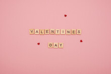 """Message """"Valentines Day"""" Made From Wooden Tiles And Three Red Love Hearts On A Pink Background"""