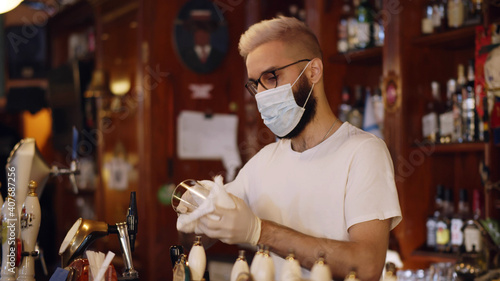 Fototapeta Bartender wearing face mask and gloves cleaning empty glass obraz