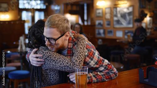 Multiethnic couple meeting and hugging in modern beer pub Fotobehang