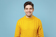 Young Caucasian Good-looking Attractive Cheerful Friendly Student Man 20s In Casual Knitted Cozy Yellow Fashionable Sweater Looking Camera With Smile Isolated On Blue Color Background Studio Portrait