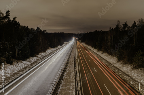 Long exposure of a road with light trails of passing vehicles Fotobehang