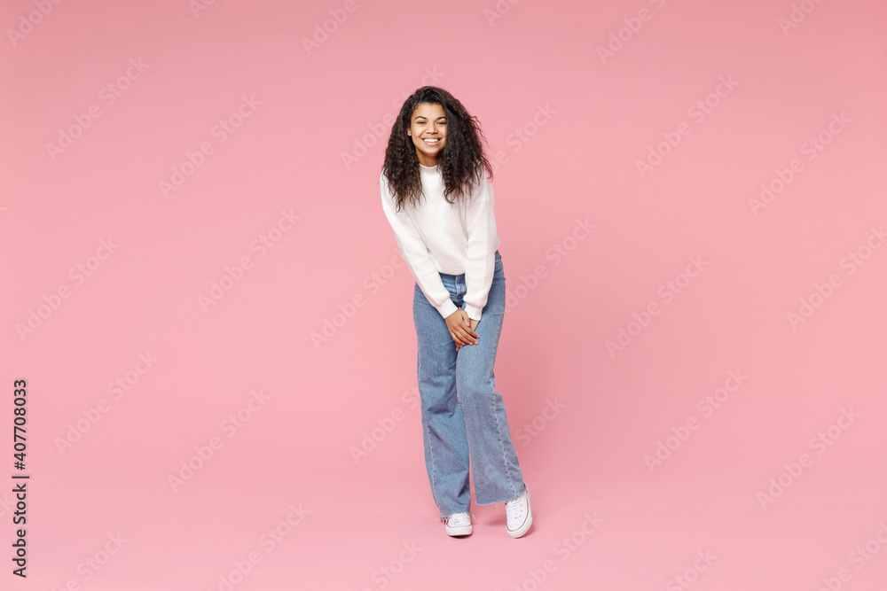 Fototapeta Full length young smiling cute african american woman 20s curly hair wear white casual knitted sweater jeans looking camera standing leaning over isolated on pastel pink background studio portrait.