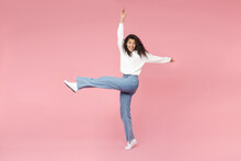 Full Length Young Cute Cheerful Happy Smiling African American Woman 20s Curly Hair In White Knitted Sweater Jeans Raised Up Hand And Leg Fooling Around Isolated On Pink Background Studio Portrait.