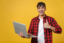 Young Spanish Latinos Smiling Happy Handsome Fashionable Friendly Man 20s Wearing Red Checkered Shirt Hold Laptop Pc Computer Show Thumb Up Like Gesture Isolated On Yellow Background Studio Portrait.