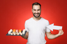 Smiling Funny Young Bearded Man 20s In Basic White T-shirt Showing Aside With Arrow On Makizushi Sushi Roll Served On Black Plate Traditional Japanese Food Isolated On Red Background Studio Portrait.