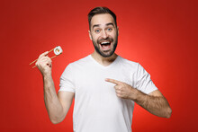 Excited Young Bearded Man 20s In Casual White T-shirt Pointing Index Finger On Sticks Chopsticks With Makizushi Sushi Roll Traditional Japanese Food Isolated On Red Color Background Studio Portrait.