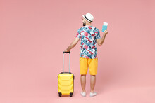 Full Length Back Rear View Of Young Traveler Tourist Man In Summer Clothes Hat Hold Suitcase Passport Tickets Isolated On Pink Background. Passenger Traveling On Weekends. Air Flight Journey Concept.