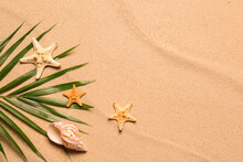 Palm Leaf, Starfishes, Seashell And Space For Text On Beach Sand, Flat Lay. Summer Vacation