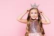 Leinwandbild Motiv cheerful little girl in dress adjusting crown isolated on pink