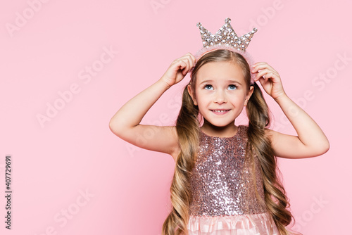 Obraz cheerful little girl in dress adjusting crown isolated on pink - fototapety do salonu