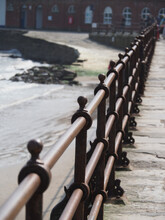 Portrait Format View Of Rusty Iron Fencing Near A Beach
