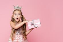 Amazed Little Girl In Crown Holding Wrapped Present Isolated On Pink