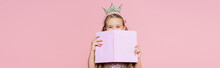 Little Girl In Crown Covering Face With Book Isolated On Pink, Banner