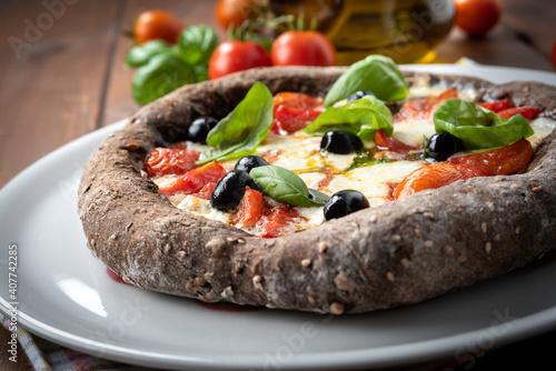 Deliziosa pizza con impasto a base di cereali e condita con pomodorini, mozzarel Fototapeta