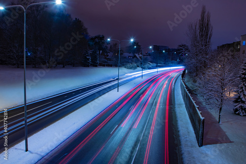 Fotografia Aerial view of a long exposure night shot of a busy freeway traffic motion near