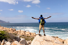 Fit Afrcan American Man Wearing Backpack Hiking Spreading Arms On The Coast