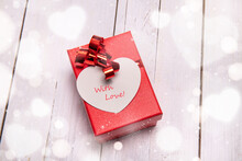 Red Box With A Big Heart-shaped Card For A Special Valentine Gift. White Wooden Background And Bokeh Effect All Around.