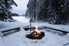 Bright Bonfire In A Winter Forest. Beautiful Snow Covered Trees. Kettle On Fire. Camping, Hiking Concept. Finland.