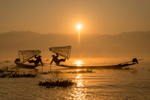 INTHA FISHERMEN, INLE LAKE, SHAN STATE, MYANMAR - 18 January 2020: Two Traditional Fishermen Using Traditional Conical Net Technique Silhouetted At Sunrise.