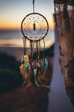 Vertical Shallow Focus Shot Of A Dream Catcher On Sea Background At Sunset