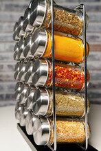 A Metal Spice Rack With Many Glass Bottles Filled With Different Spices