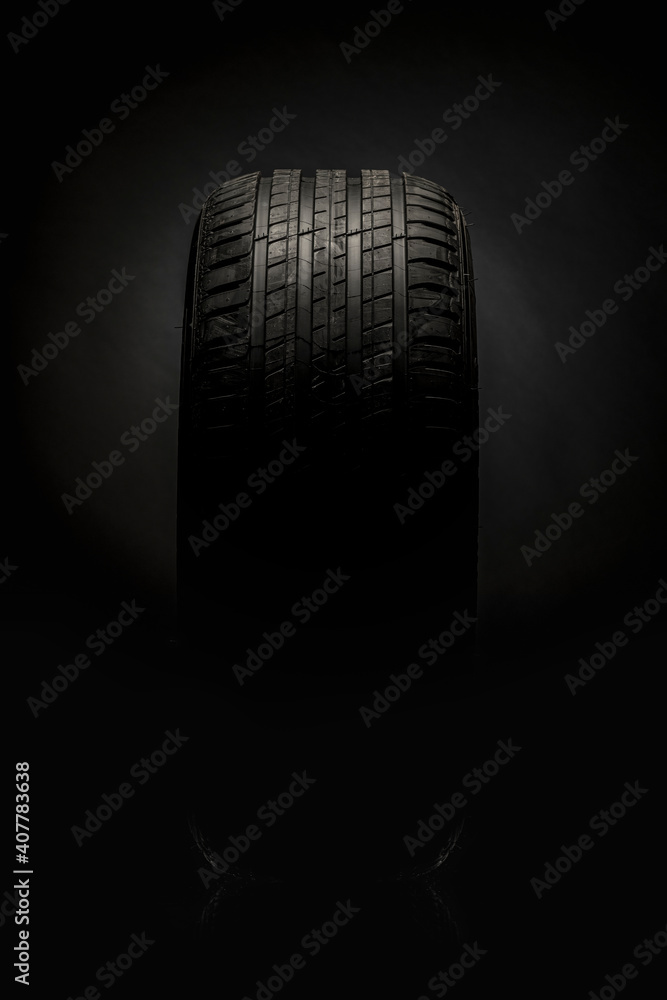 Fototapeta Horizontal isolated in darkness TYRE and tyre pattern, auto equipment having the top surface lighted on black background