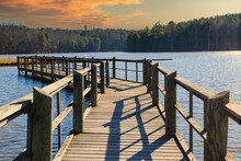 A Long Gray Wooden Bridge On The Vast Blue Lake Water Of Lake McIntosh With Stunning Skies And Lush Green And Autumn Colored Trees On The Banks Of The Lake At Lake McIntosh In Peachtree City Georgia