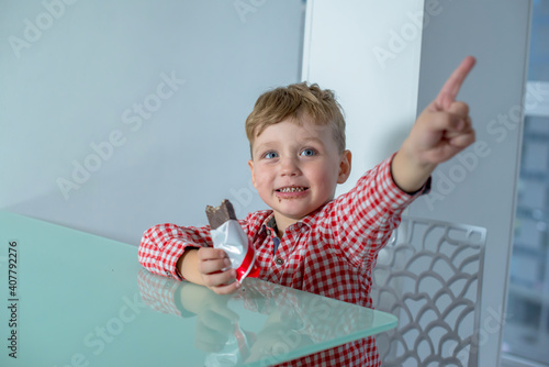 Fotografia Boy holds a chocolate bar in his hand and points to the side