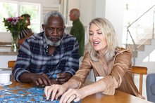 Senior Caucasian Woman And African American Man Sitting By Table Doing Puzzles At Home