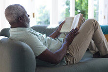 Senior African American Man Lying On Couch Reading Book