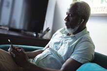 Senior African American Man Sitting In Living Room Using Smartphone Listening To Music On Earphones