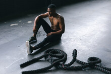 African American Man Wearing Sports Clothes Sitting Resting After Battling Ropes In Empty Urban Buil