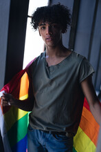 Mixed Race Man Holding Rainbow Flag Looking At Camera