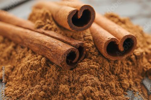 Fotografija Cinnamon sticks and powder on wooden background, closeup