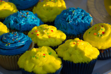 Colorful Blue And Yellow Homemade Cupcakes With Sprinkles, Minion Concept Party, Desserts In Blue And Yellow Color On A Table