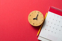 Close Up Of Calendar And Alarm Clock On The Red Table Background, Planning For Business Meeting Or Travel Planning Concept