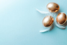 Golden Easter Colour Eggs With White Feathers On Pastel Blue Background In Happy Easter Decoration. Spring Holiday Top View Concept.