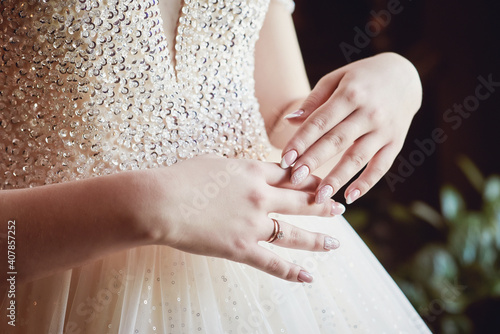 Canvastavla hands of the bride with a stylish manicure on the bodice of a luxurious wedding