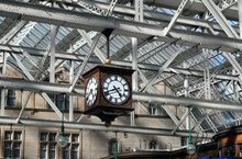 Pattern Of Steel Roof Beams And Glass In Old Railway Station Building With Large Hanging Clock
