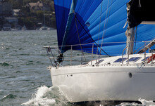 A 38-foot Sailboat In Sydney Harbor With Its Bright Blue Spinnaker Fully Deployed On A Port Tack. View Of The Boat's Bow