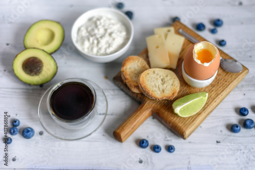 Fotografía A healthy and nutritious breakfast: a bowl of cottage cheese, hard cheese, boiled egg, baguette slices with avocado and cup of hot coffee or tea