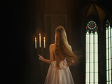 Mysterious art medieval girl princess walks in dark gothic room. Woman queen is holding candlestick with burning candles in hand. Dress with open back long loose blonde hair flying in motion. Go away