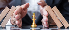 Business Man Hand Protect Chess King Figure And Stopping Falling Wooden Blocks Or Dominoes. Business, Risk Management, Solution, Economic Regression, Insurance, Strategy And Interruption Concepts