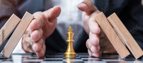 Foto Business man hand protect Chess King figure and Stopping Falling wooden Blocks or Dominoes