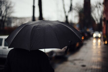 Man With Ablack Umbrella Walking In The Street With A Blurred Background