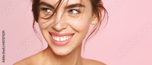 Close-up of fresh natural woman with nude makeup, white smile, looking aside on pink background. Romantic girl with clean hydrated skin, well-nourished smooth face