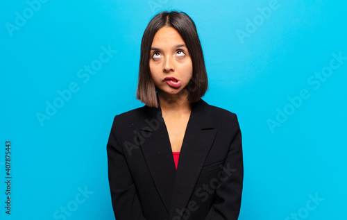 Fototapeta hispanic woman looking goofy and funny with a silly cross-eyed expression, jokin