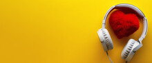 Red Heart And White Headphones On A Yellow Background. Love Music Lifestyle Concept. Valentine's Day. Banner