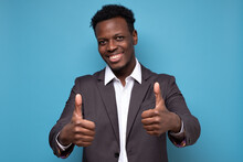 Young African Businessman Showing Thumb Up Approving Your Choice. Studio Shot On Blue Wall.