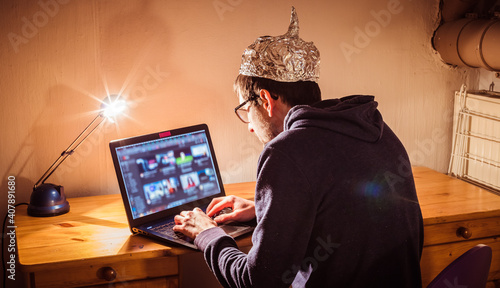 Billede på lærred Conspiracy theory concept: young man with aluminum cap searching the internet, s